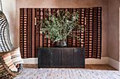 Olivenzweige auf schwarzem Sideboard vor Wandteppich