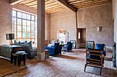 Wohnzimmer mit blauen Polstermöbeln im Lehmhaus