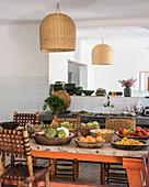 Holzschalen mit Obst und Gemüse auf dem Tisch mit rustikalen Stühlen