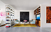 TV area with room divider shelf and light blue seating