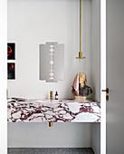 Marmor-Waschtisch mit Büste, darüber Pendelleuchte und Spiegel in Rasierklingen-Form im Bad