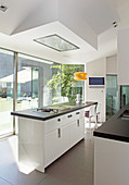 Moderne Designerküche mit Kochinsel und Fensterfront