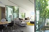 Modernes Wohnzimmer mit Glaswänden zum Bambusgarten