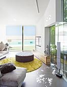 Polsterhocker im modernen Wohnzimmer mit Glaswänden