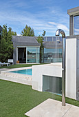 Water splashing from outdoor shower next to pool outside modern house
