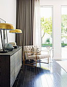 Table lamps on sideboard next to armchair and side table in front of terrace doors in bedroom