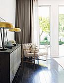 Kommode mit Tischleuchten und Sessel mit Beistelltisch vor Terrassentür im Schlafzimmer