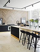 Black cupboards, black bar stools and island counter with extended worksurface in elegant kitchen