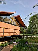 Modernes Haus mit offenem Dach im sommerlichen Park