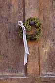 Small heart-shaped wreath of ivy berries with ribbon on doorknob