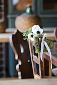 Anemones and heart-shaped wreath of ivy berries on chair backrest