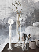 Cutlery, kitchen utensils and twigs in tall glass measuring beaker