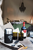 Cutlery, thermos flask, glasses and bottle of red wine on wooden table outside tent