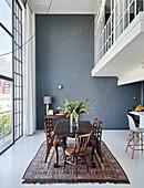 Esstisch mit Stühlen vor Fensterfront in hohem Raum