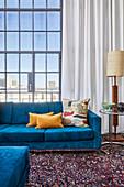 Blaue Polstermöbel mit Kissen, Beistelltisch und Stehleuchte vor Fensterfront in hohem Wohnraum