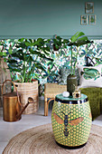 Ceramic stool with bee motif in front of jungle-patterned wallpaper