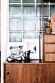 Retro sideboard with decorative objects and framed photos in front of a glass brick wall