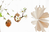 Paper decorations and Easter eggs hung from blossoming fruit branch