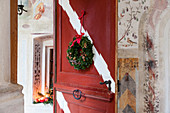 Wintry decorations in entrance area: arrangement in window niche and wreath on red wooden door