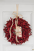 Wreath of red berries with postcard on white door