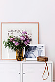 Bouquet of purple roses and pictures on the sideboard