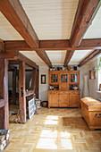 Alte Holztruhe und Anrichte im Raum mit Holzbalkendecke