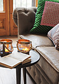 Open book and two candle lanterns on table next to sofa