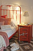 Metal crate used as bedside table next to red bed in child's bedroom