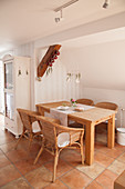 Solid wooden table and rattan armchairs below sloping ceiling in dining area