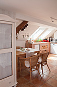 Solid wooden table and rattan armchairs below sloping ceiling in open-plan kitchen