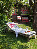 Sun lounger with cushions outside wooden cabin in garden