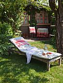 Liege mit Polster im Garten vor einem Holzhäuschen