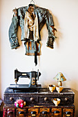 Designer jacket on wall above vintage sewing machine and papier-mâché cups on chest of drawers