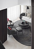 View of dark gray designer armchairs, coffee table and sofa in the living room