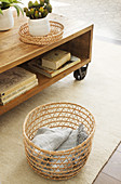 Blanket in airy basket next to wooden coffee table on castors