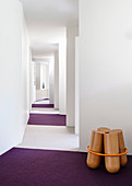 Wooden sculpture on purple carpet in white hallway