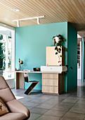 Zig-Zag-Stuhl und Schreibtisch an türkisfarbenem Raumteiler in offenem Wohnraum