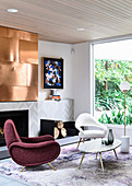 Lounge area with designer seating and fireplace, copper plate above