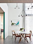 White dining table with chairs, designer lamp above