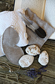 Still-life arrangement of limestone pebbles, lavender, sleeping mask, heat cushion and feather