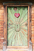 Love-heart sign on rustic wooden door