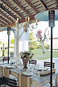 Festively set table on roofed terrace in garden