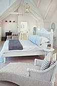 Wicker armchair and bed in white attic bedroom