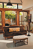 Baroque sofa and upholstered footstool in front of open, arched terrace doors
