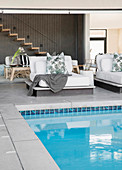Leaf-patterned scatter cushions on upholstered loungers next to pool