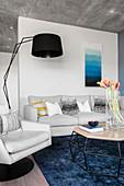 Couchtisch mit geometrischer Form vor weißem Sessel und Sofa