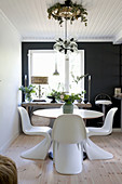 Designer chairs at round table in dining room with black accent wall