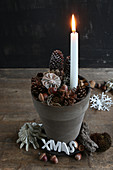 Lit candle in clay pot with festive decorations