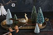 Peacock figurine on twig in front of Christmas tree ornaments on tray