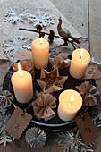 Brennende Kerzen auf einem Teller mit Stoffblumen und Papiersternen
